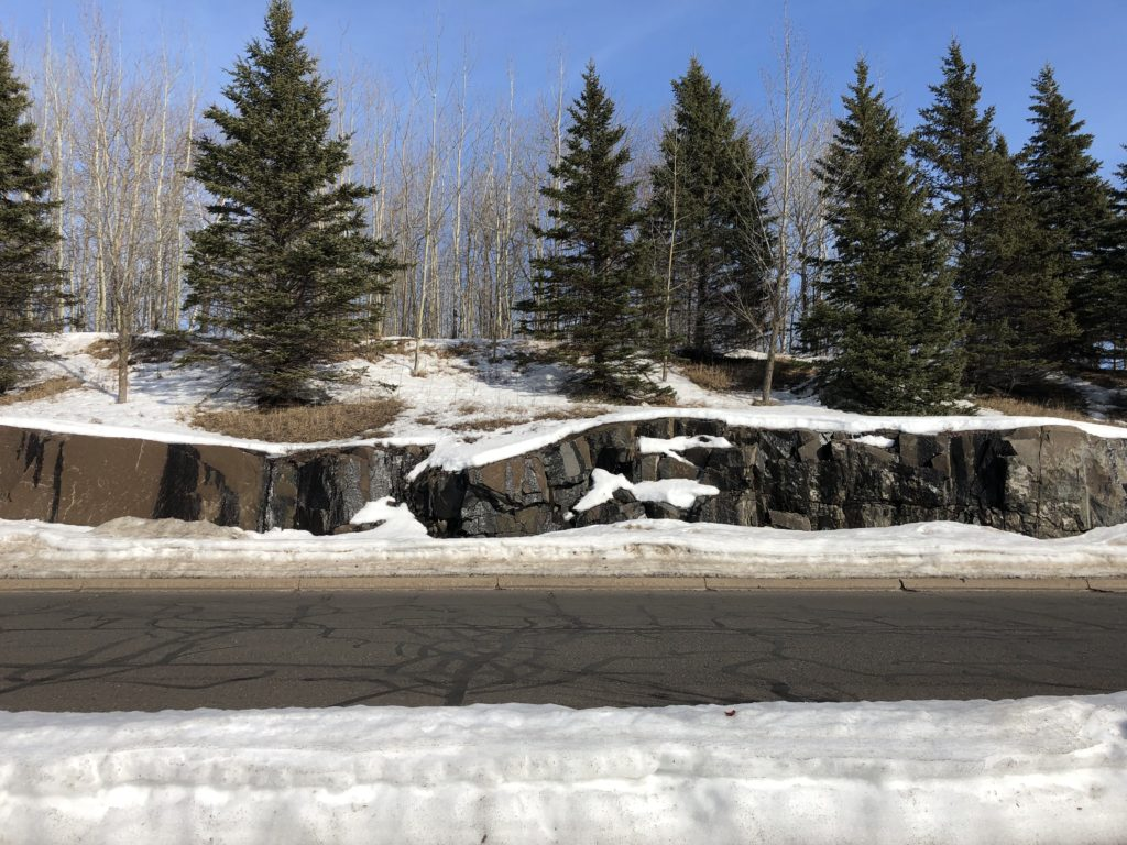 Photo of rock, evergreens road and snow.